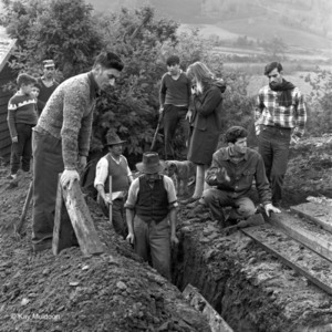 Photograph of volunteers and community members working on drainage ditches to make roads passable for Trovolhue construction projects in Chile.