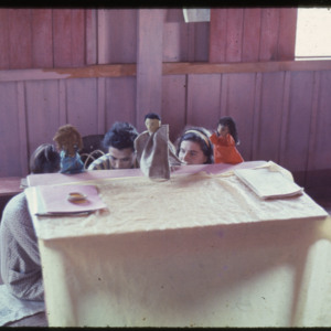 Photograph of three Peace Corps Volunteers performing at puppet show in Mallorquin during a 4-C fair.