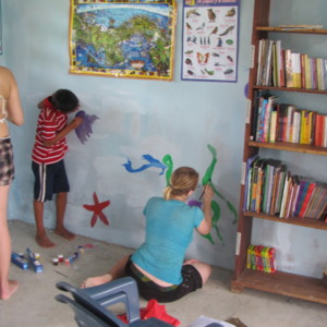 Photograph of Rachel Teter, another volunteer, and local children working on the mural at the new community library in El Plátano, Panama, 10 May 2013.
