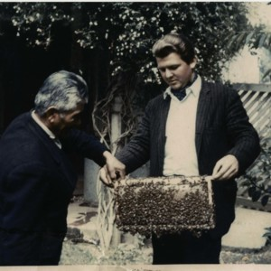 Photograph of Gage Skinner demonstrating how to handle bees to Richard Antileo, a Mapuche Indian, at the reservation near Lumaco, Chile.