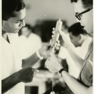 Photograph of Stephen Bossi and Ram Murthy building a spring balance from bamboo at a science workshop.