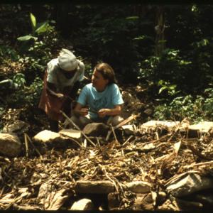 Photograph of Meghan Keith-Hynes speaking to a Haitian woman near a stone circle plot.