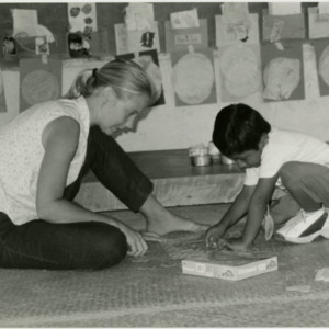 Photograph of volunteer Ellen Vahue working with a student in the Jumpstart English Program in Cristo Rey Village, Cayo, Belize in 2002.