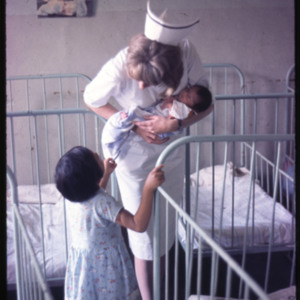 Photograph of Peggy Gleeson Wyllie, a Nurse volunteer, holding an infant in the baby ward of Fusa Hospital in Fusa, Colombia.